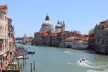 View of Venice with boats in the Grand Canal and the big Dome of Basilica called Madonna della Salute