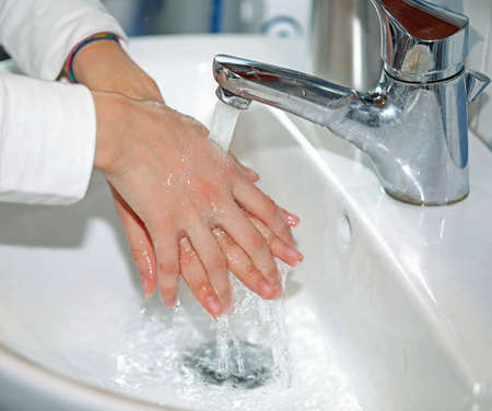 young girl while washing her hands in the sink with water