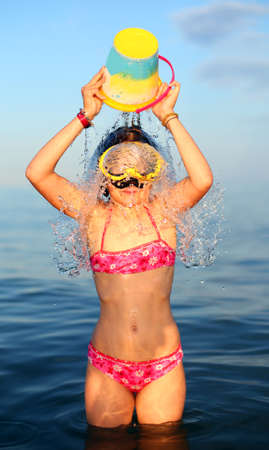 little girl in a swimsuit plays with the bucket in the sea in summer Stock Photo