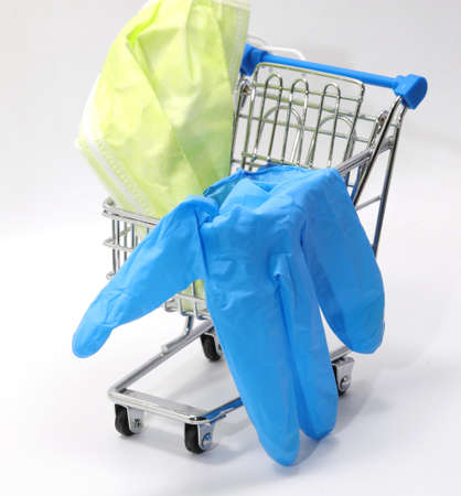 Small shopping trolley with protective latex glove and surgical mask on white