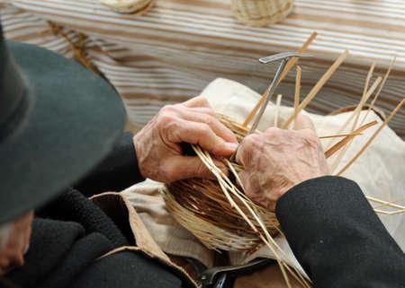 elderly gentleman with a hat makes a wicker basket Stock fotó