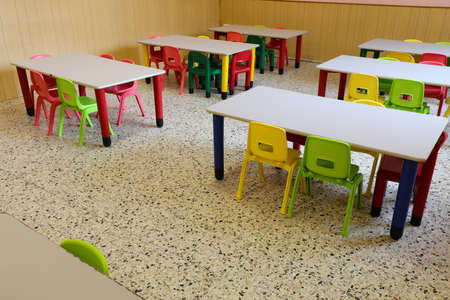 small chairs and tables of a classroom without children who have been home due to the flu epidemic Archivio Fotografico