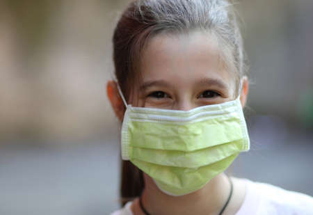 smiling eyes of a pretty little girl with green surgical mask during the lock down caused by the Corona Virus