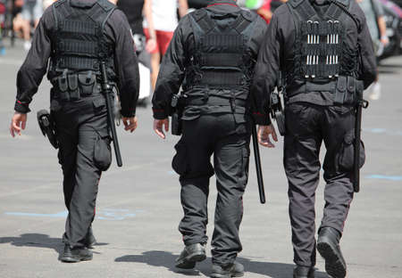 three policemen during the patrol of the city with riot uniform and batons