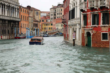 boat crosses the Grand Canal in Venice between ancient buildings