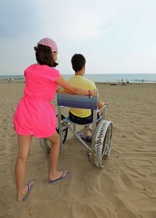pretty caucasian little girl pushes the wheelchair with her brother on the sandy beach Archivio Fotografico