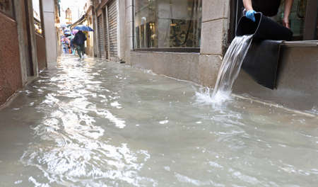 person emptying the interior of the shop flooded after the flood in Venice and the narrow alley covered with sea water Archivio Fotografico