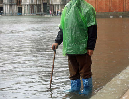elderly gentleman with walking stick in Saint Mark square in Venice in Italy during high tide