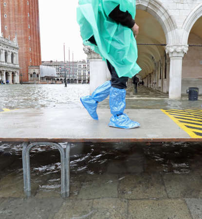 hasty tourist walks fast on the elevated walkway during high tide in Venice in Italy