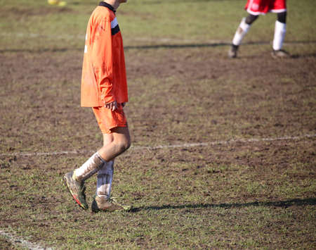 Young soccer player in the mud during the football match