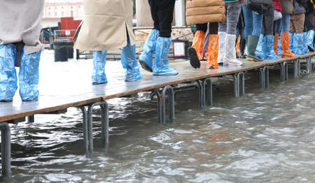 hurried people walk quickly on the elevated walkway during high tide in Venice near Saint Mark Square Stock Photo