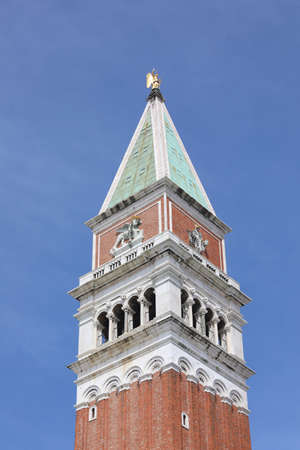 Statue of the archangel Gabriel on the tip of the Bell Tower of Saint Mark in Venice and the blue sky in the background