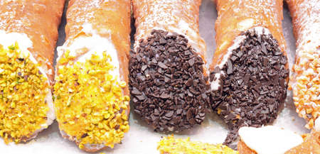 stuffed Sicilian cannoli with ricotta cheese chocolate and almonds for sale in the Italian pastry shop