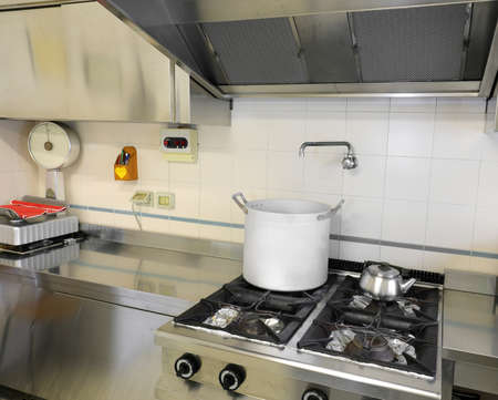 interior of industrial kitchen with stainless steel stove and large aluminum saucepan