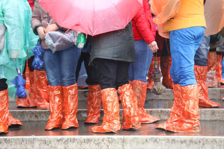 many people with special waterproof gaiters on the steps of the bridge in Venice during the rain