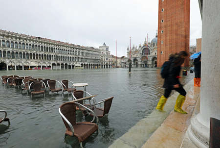Chairs of an alfresco cafe in the fully flooded Square of Saint Mark in Venice in Italy during high tide with and some people