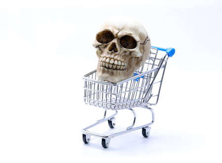 human skull with clearly visible teeth inside the shopping cart on a white background