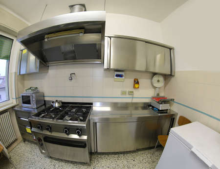 industrial kitchen photographed with fisheye lens without the cooks with stove and stainless steel furniture