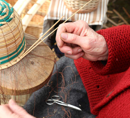 hands with arthrosis of the elderly lady while she creates a wicker basket for sale at the market