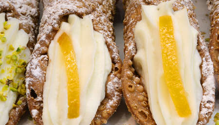 Italian pastries with orange and cheese called CANNOLI for sale at sicilian store