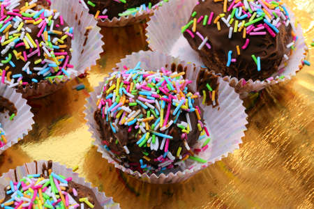 many pastries called cake pops on golden background