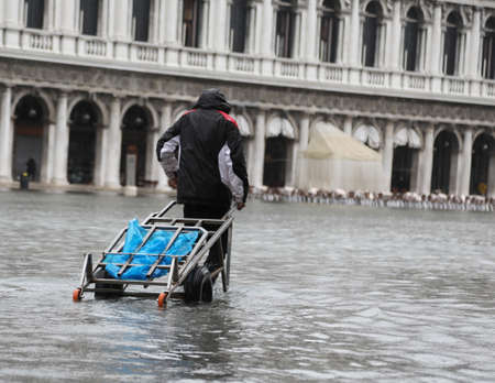 Porter with cart in Venice in Italy during flood