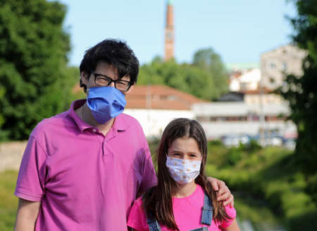 Father and his daughter with surgical mask caused by Corona Virus
