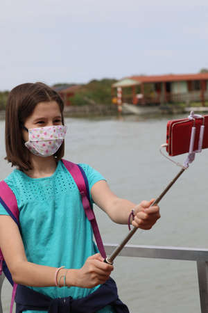 girl with surgical mask because of the Corona Virus takes a selfie with the smart phone and the selfiestick Stock Photo