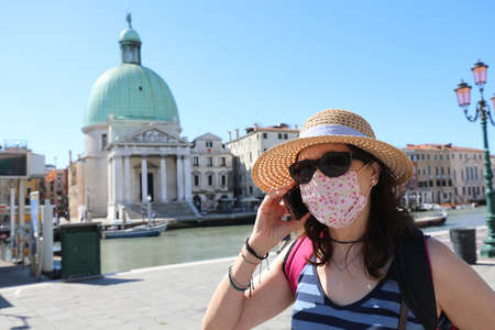 woman with straw hat sunglasses and surgical mask while talking on the phone in Venice during the trip at the time of the Coronavirus pandemic