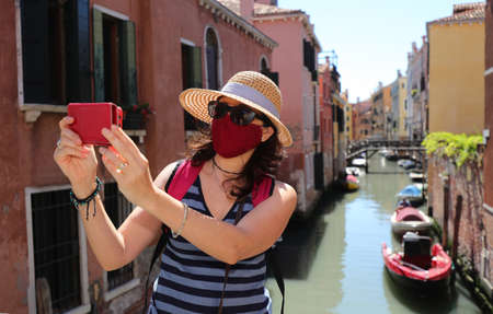 woman with straw hat while takes pictures of Venice and the surgical mask caused Corona virus