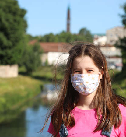 Young pretty girl with surgical mask and smiling eyes