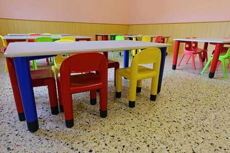 Inside a school classroom completely empty with small plastic chairs