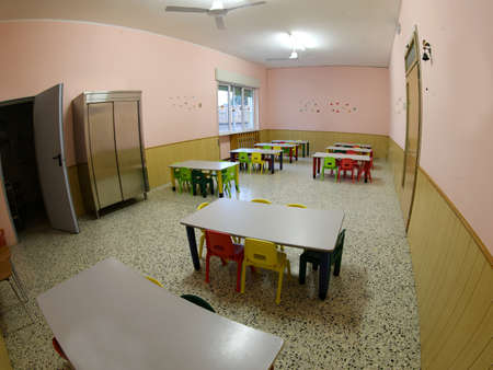 interior of a canteen of the elementary school completely empty with small plastic chairs