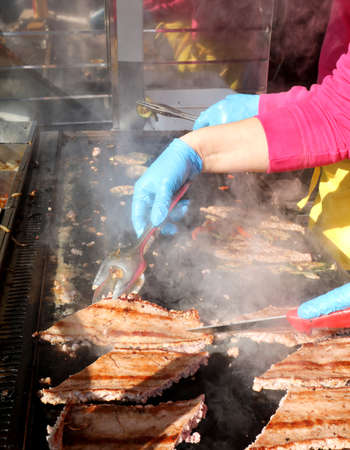 cooks latex gloves with blue while cooking sausages at an alfresco  street food stall Banco de Imagens