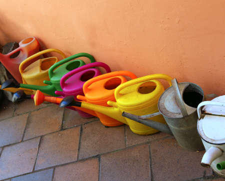 set of colored watering cans in the garden
