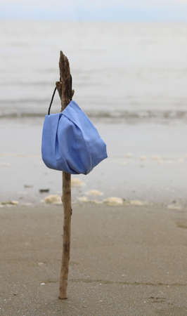 anti-covid surgical mask on a branch by the sea symbol of the end of the infection by the terrible Coronavirus
