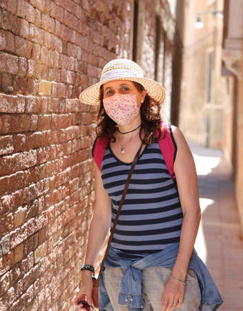 Woman with straw hat and surgical mask during the Corona Virus pandemic while visiting the island of Venice in Italy