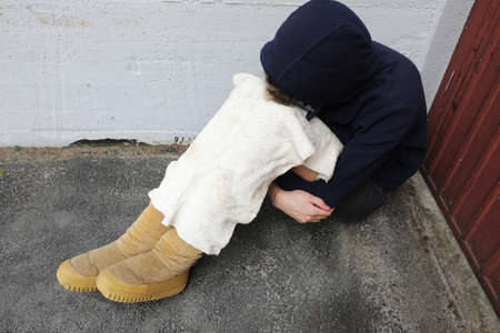 young homeless man with hooded sweatshirt and old worn out boots on a street corner of the metropolis
