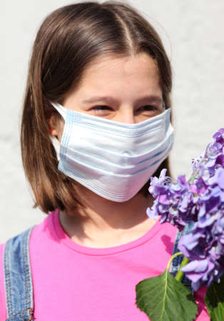 little girl with mask for protection against Covid-19 and hydrangea flowers Stock Photo