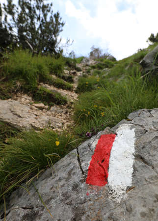 white and red sign in the mountain path above the big stone