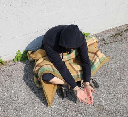 homeless man begging on the street under an old blanket