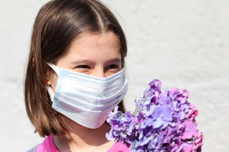 girl with surgical mask for protection against Covid-19 and has hydrangea flowers 스톡 콘텐츠