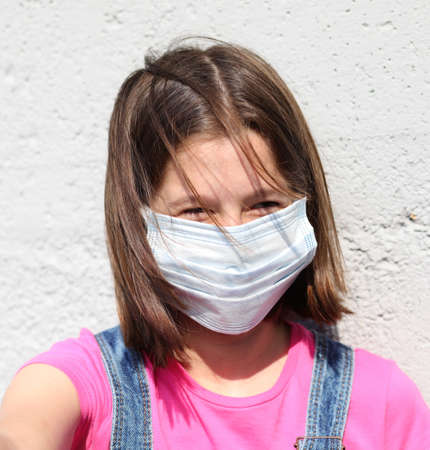 smiling eyes of little girl with surgical mask for protection against Corona Virus with brown hair blowing in the wind Stock Photo
