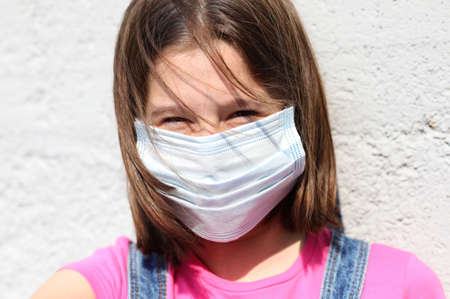 smiling eyes of little girl with surgical mask for protection against Covid-19 with brown hair blowing in the wind