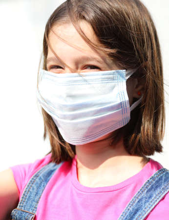 Extreme close up of a smiling young girl with surgical mask for protection against the Corona Virus during lockdown in the world Stock Photo