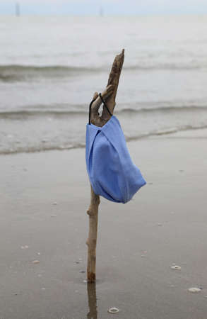 anti-covid surgical mask on a branch by the sea after the end of the infection in summer