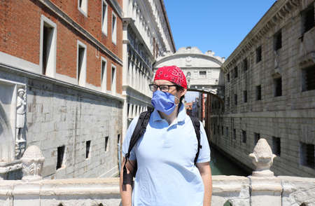 man with surgical mask and red bandana during lockdown caused by Corona Virus in Venice in Italy