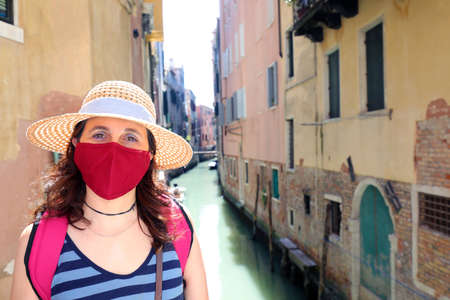 Pretty Lady with surgical mask and straw hat tourist visit in the island of Venice in Italy during the lockdown caused by the Corona Virus