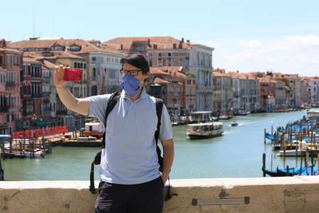 young man with surgical mask takes a selfie on the Rialto bridge in Venice in Italy during the emergency from Corona Virus