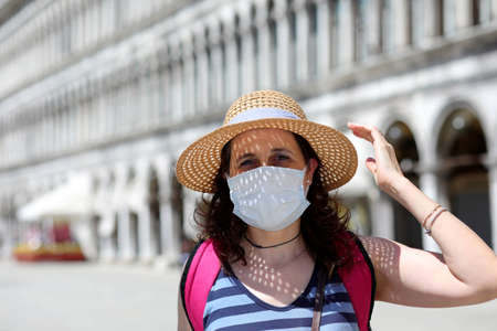 beautiful woman with hat and surgical mask during travel to Venice Italy in the period of the Corona virus epidemic Stock Photo